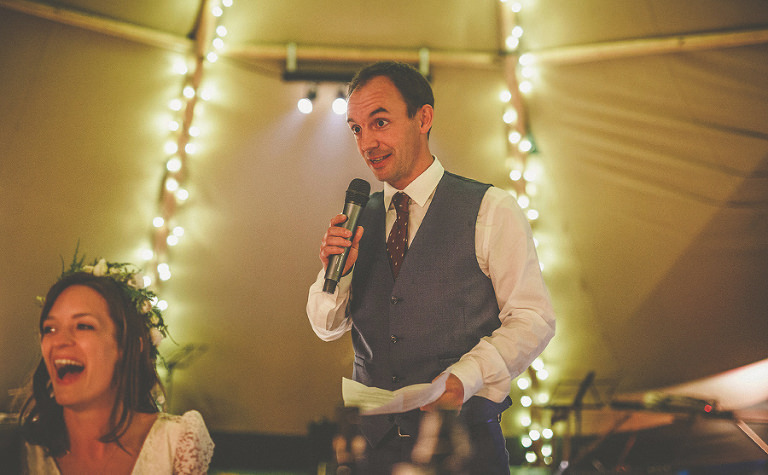 The groom speaks in front of the wedding guests in the marquee