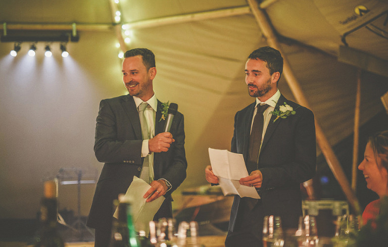 The best men stand up and speak in the marquee in front of the wedding guests