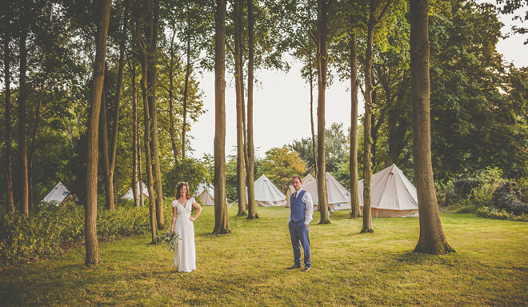 The bride and groom stand apart from each other in the camping fields