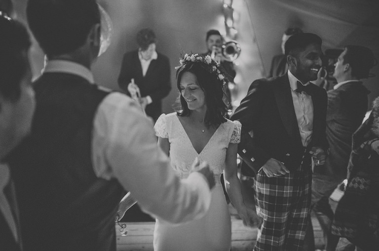 The groom smiles as she dances with friends and family on the dancefloor of the marquee