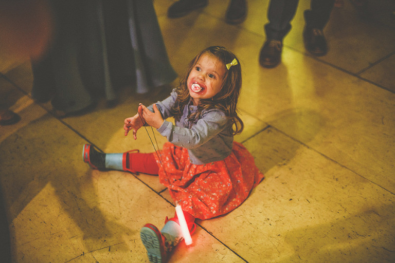 A little girl sat on the dancefloor in the marquee