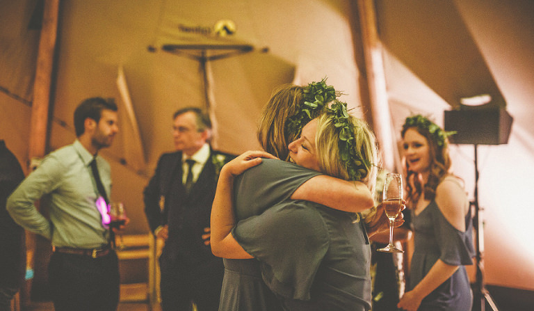 A bridesmaid embraces her friend on the dancefloor of the marquee