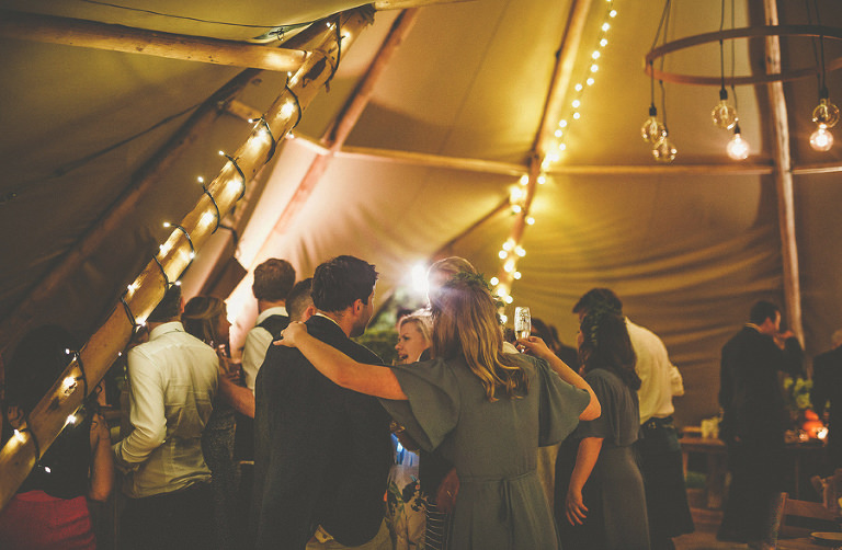 Wedding guests embrace each other in the marquee