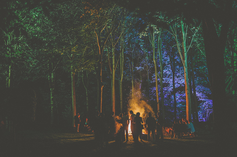 Wedding guests stood around the campfire next to the woods of the wedding venue late at night