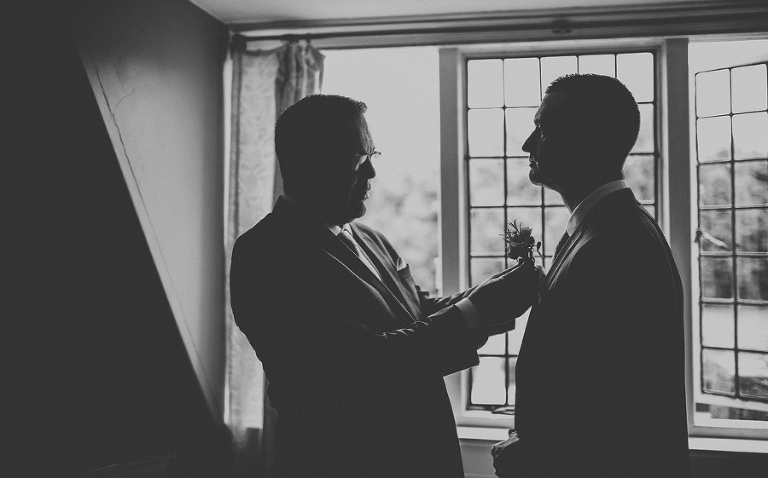 The best man places a flower on the lapel of the grooms suit