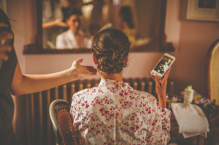 The hairdresser straightens the back of the brides hair