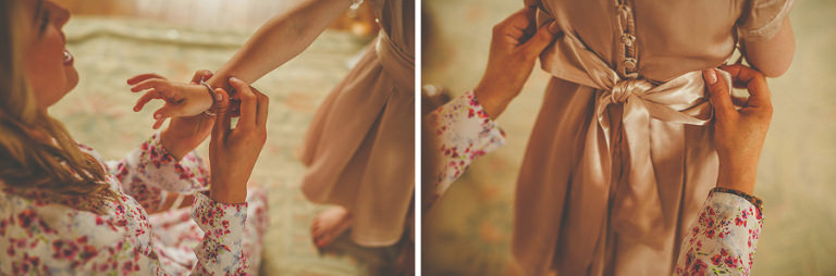 A bridesmaid fastens the ribbons to the back of the flowergirls dress