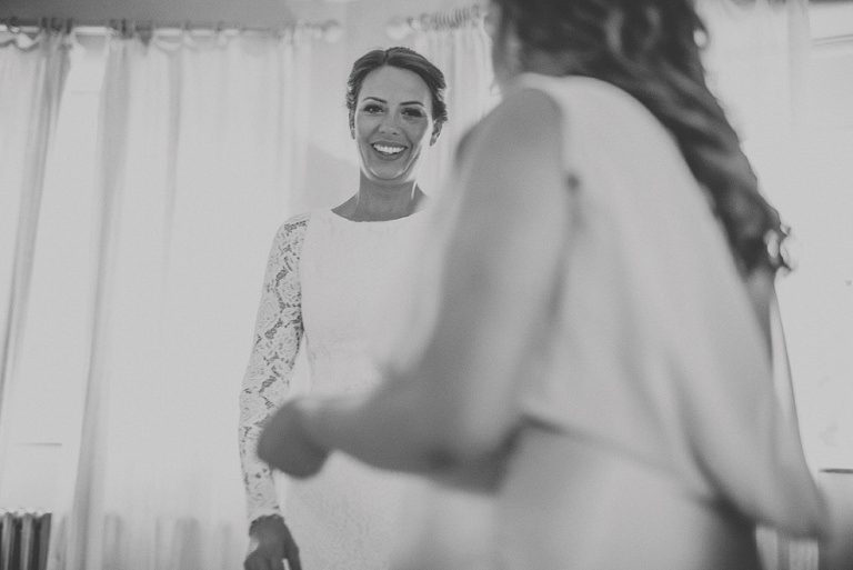 The bride smiles at a bridesmaid