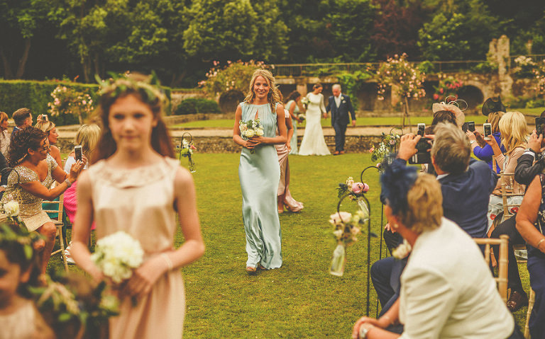 A bridesmaid and flowergirls walk down the aisle of the outdoor ceremony at Voewood
