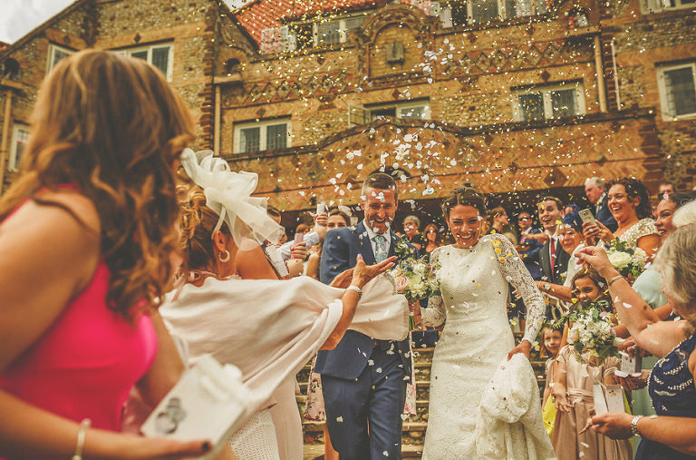 The wedding party throw confetti as the bride and groom walk down the stone steps at the front of Voewood