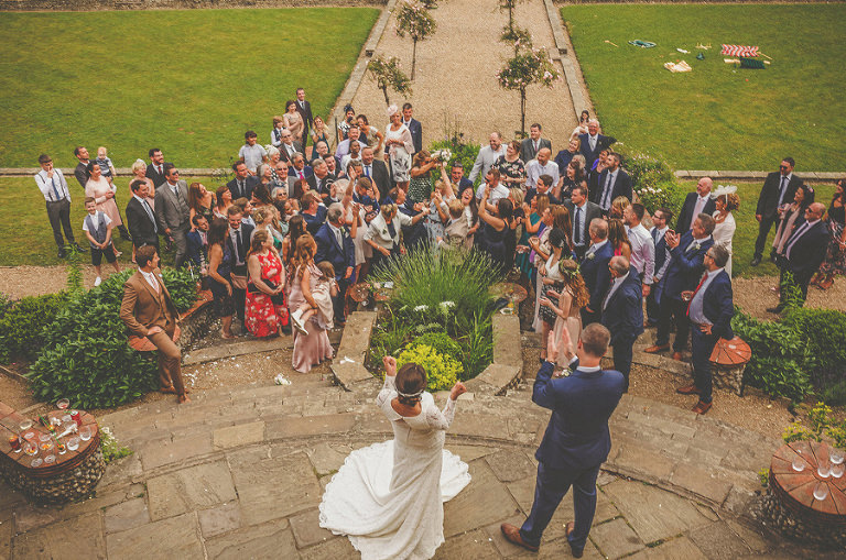 A wedding guest catches the bouquet thrown by the bride on the steps at Voewood