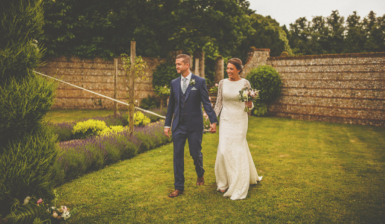 The bride and groom walk towards the marquee at the back of Voewood house