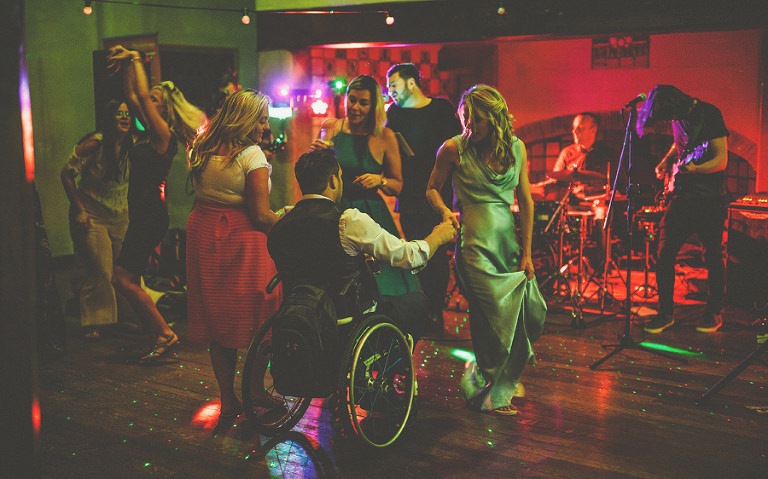 A man in a whellchair dances with a bridesmaid on the dancefloor at Voewood