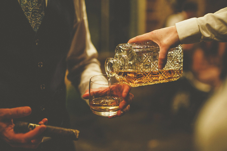 An usher pours whisky into a glass