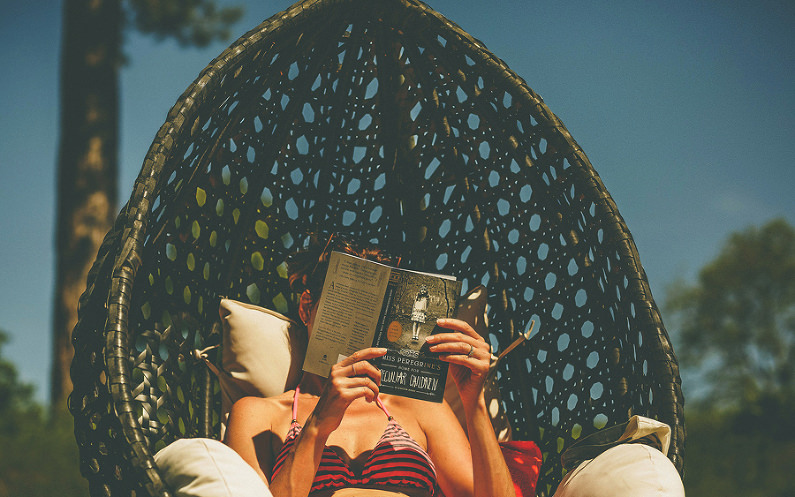 A wedding guest reads a book next to the outdoor pool at Wilderness reserve