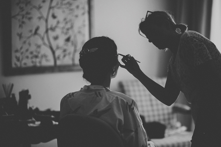 The make up artist applies make up on the brides eyebrows