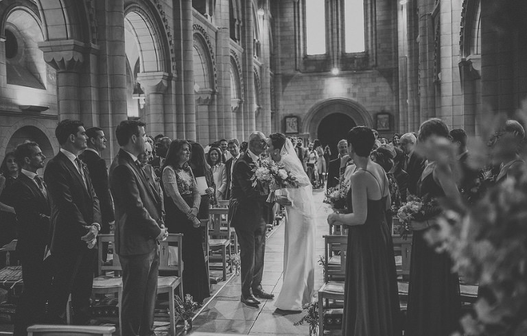 The bride kisses her father in the aisle of the church