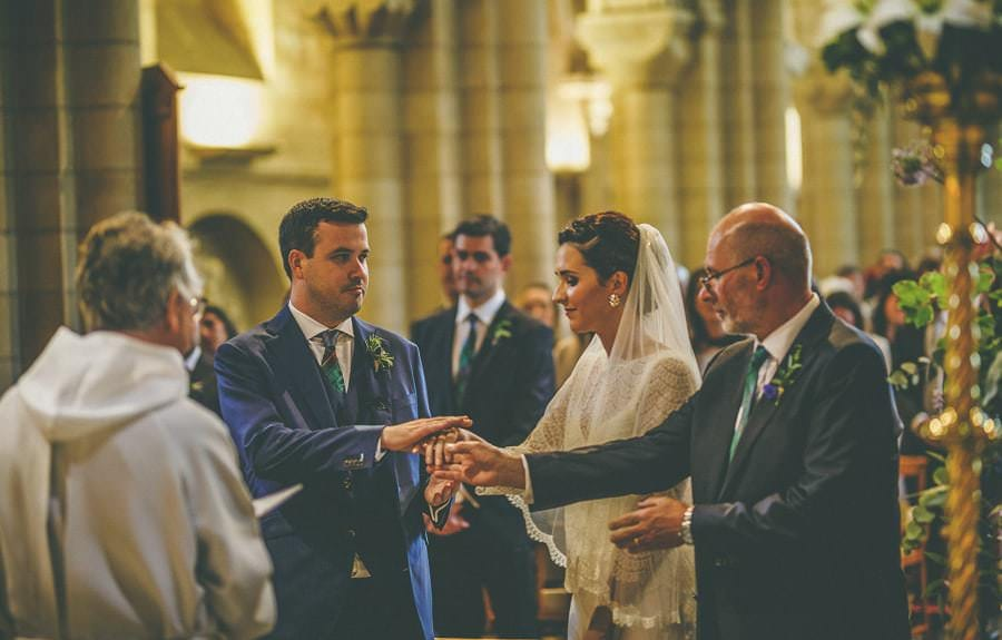 The groom takes the hand of the bride during the ceremony
