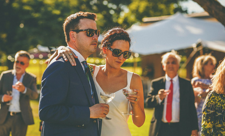 The bride and groom drink champagne together on the lawn