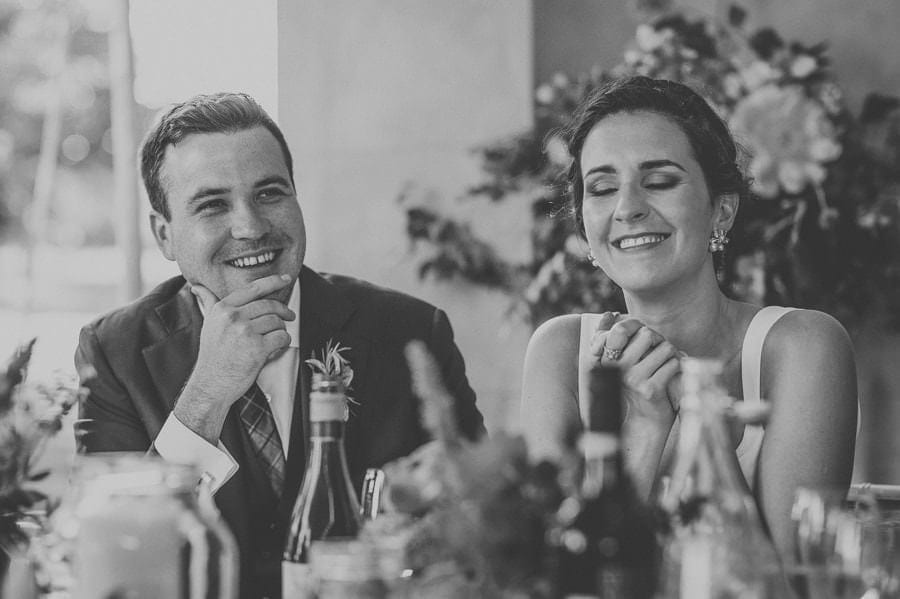 The bride and groom laugh during the speeches
