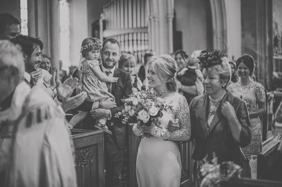 The bride walks up the aisle with her mother in the church of St. Mary the virgin Batcombe