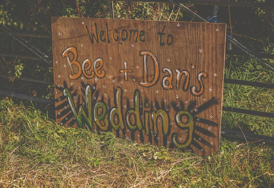 Welcome to Bee and Dannys wedding sign on a field outside the barn