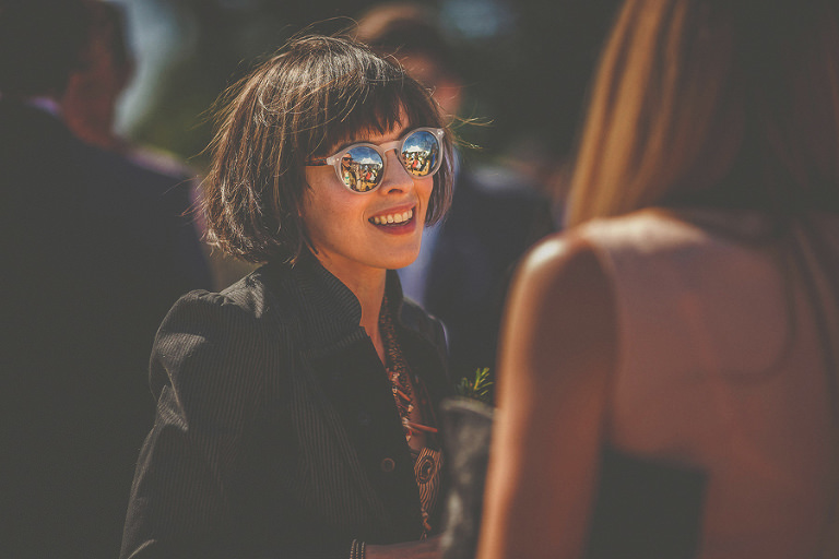 A wedding guest in sunglasses talks to a friend