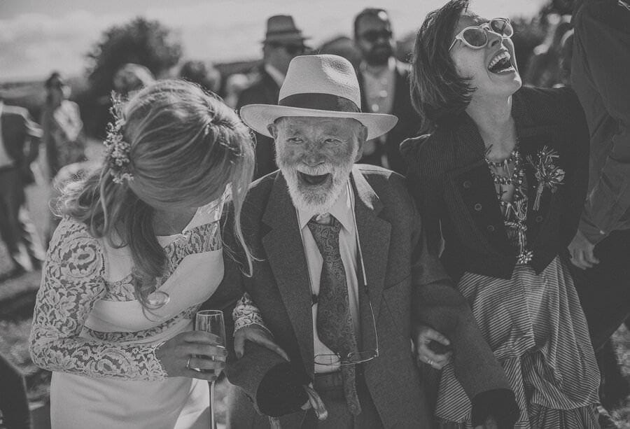 The brides grandfather laughs with the bride