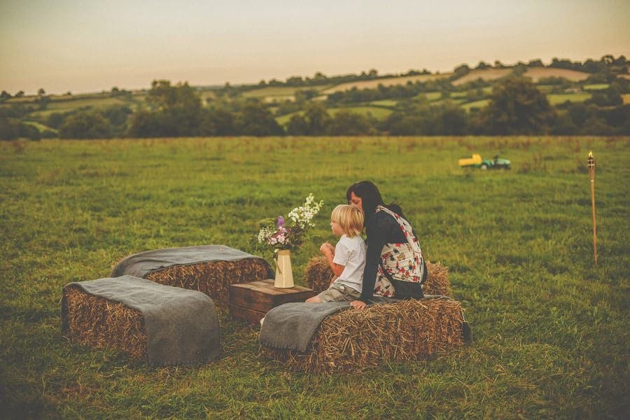 A mother and her boy sit in the field as the sun sets