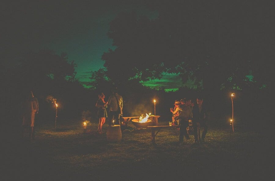 A fire is lit and wedding guests gather round