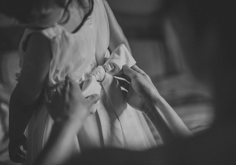 Fastening a bow to the flower girls dress