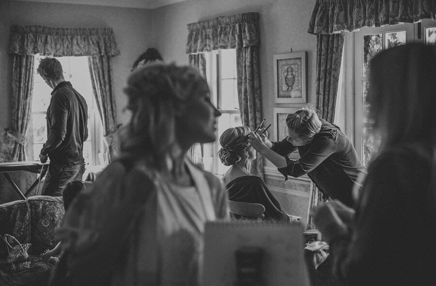 The make up artist applies make up to the bride