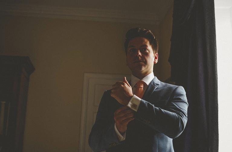 The groom adjusts his cufflinks