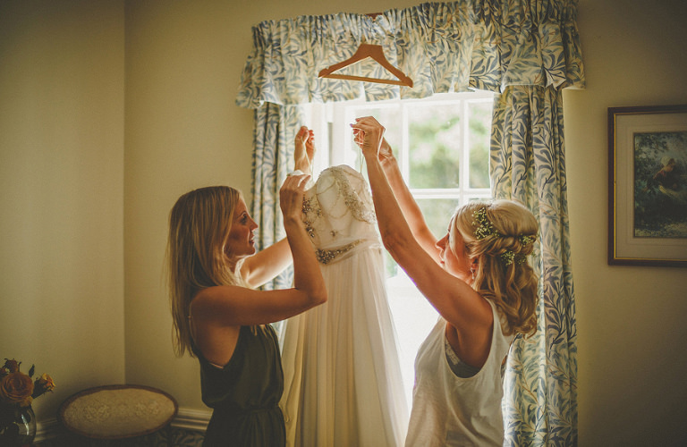 The bride and her friend take the wedding dress off the clothes hanger