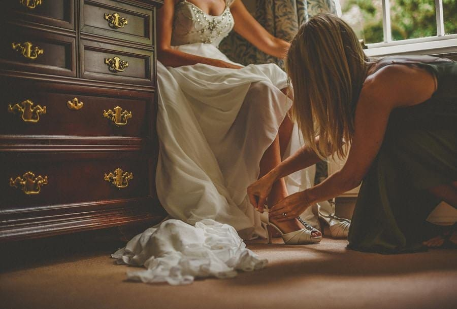 A friend puts on the shoes for the bride
