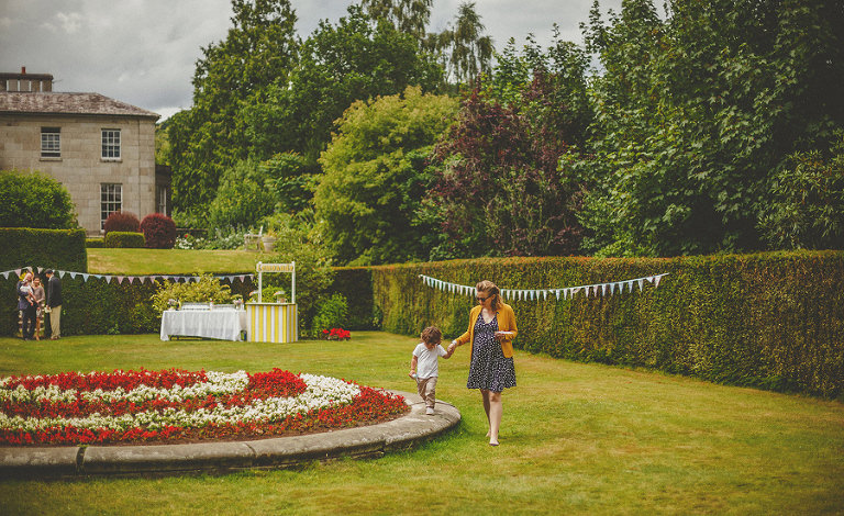 A little boy and his mother walk through the gardens at Cole Hayes Park