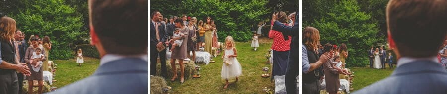 The flower girl drops rose petals along the way to the outdoor ceremony