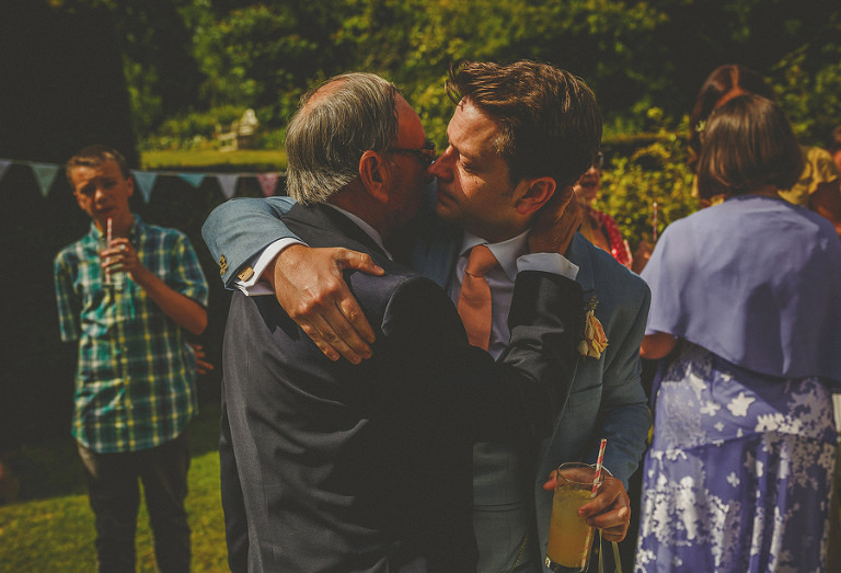 The groom crying as he embraces his father