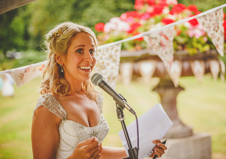 The bride smiles during her speech