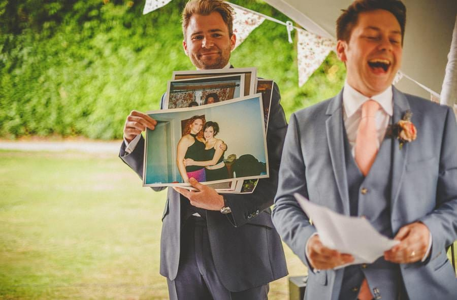 A photograph of the bride makes the groom laugh during the speeches