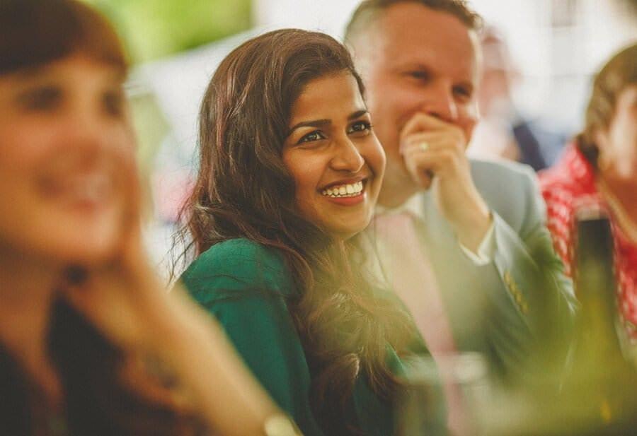 A wedding guest laughs at the best mans speech