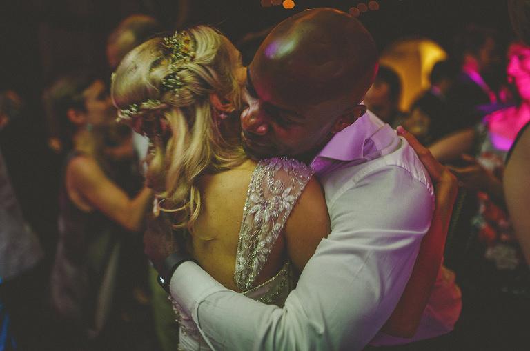 The bride embraces a friend on the dancefloor
