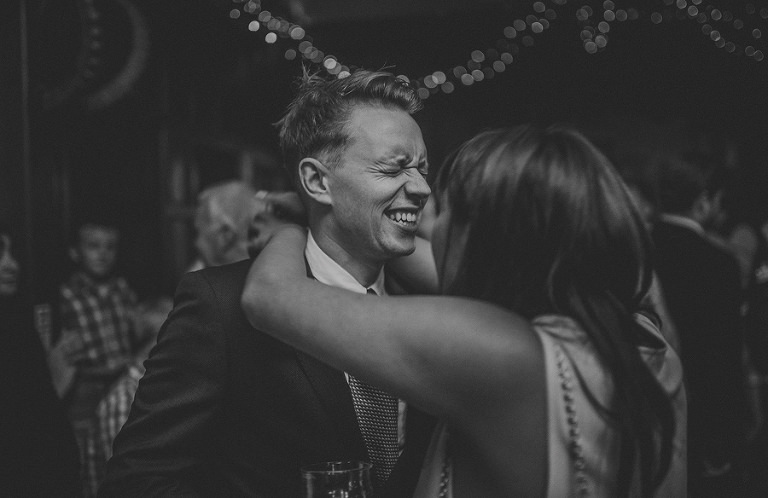 A member of the wedding party laughs with a lady on the dancefloor