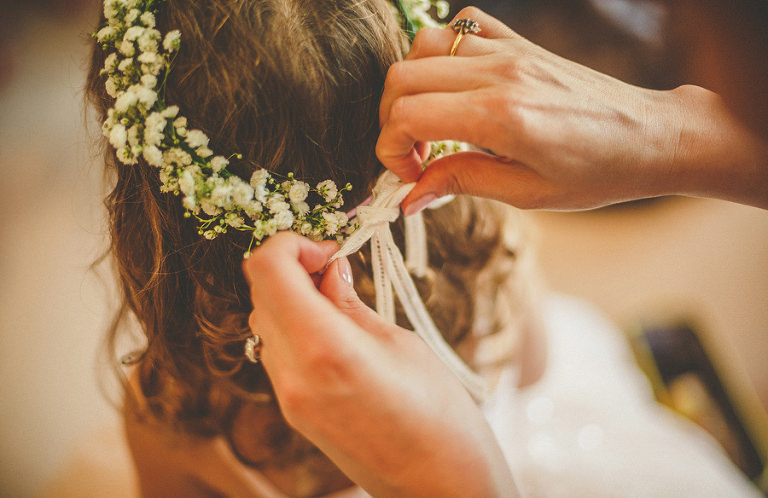 A bridesmaids tightens the strap on a head dress