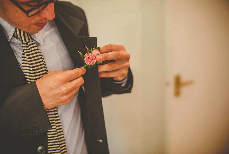 The brides brother arranges the rose on his lapel