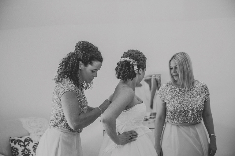 The bridesmaids help with putting on the dress