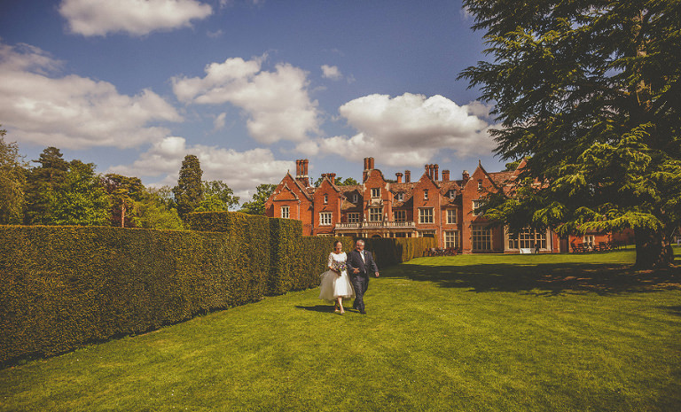 The bride and her father walk through the gardens at Longstowe Hall