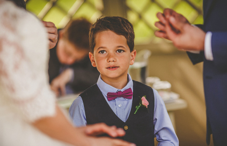 An usher boy watches as the bride and groom exchange rings during the ceremony