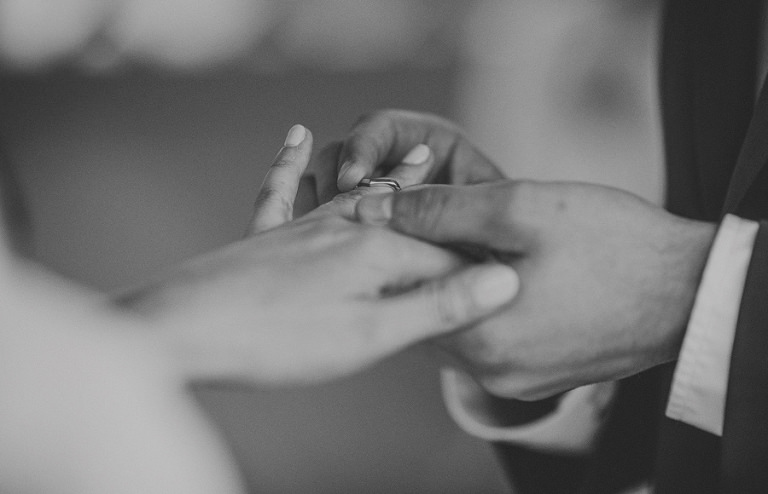 The groom places a ring on the finger of the bride during the ceremony