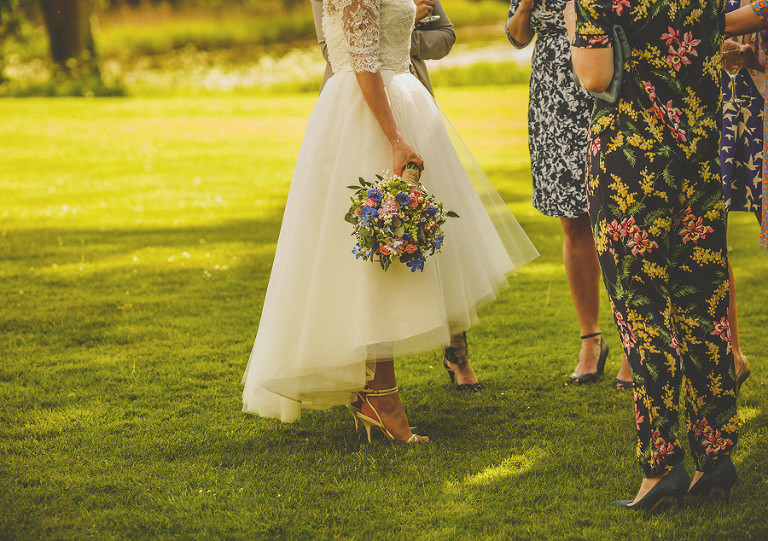 The bride holds her bouquet in the garden at Longstowe Hall